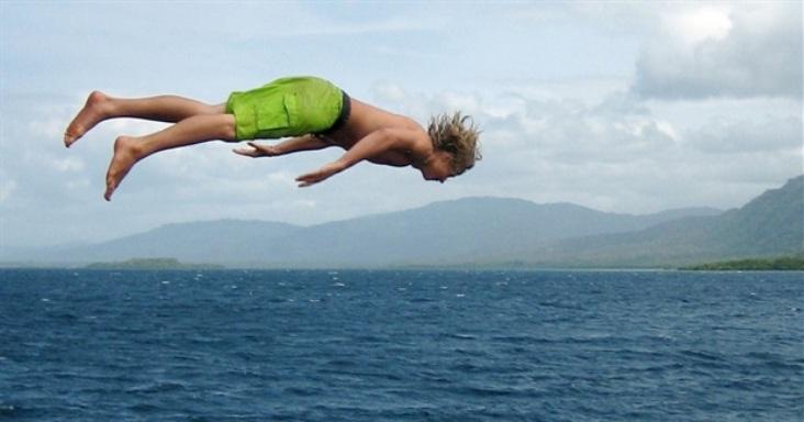 child-diving-into-sea